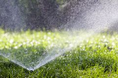 Lawn water sprinkler spraying water over grass in garden on a hot summer day. Automatic watering lawns. Gardening and environment. Concept stock photos