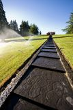 Lawn watering. In park with automated sprinkler system Royalty Free Stock Images