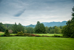 Lawn in Western North Carolina. A grassy lawn stretches out in front of a distant view of the Blue Ridge Mountains stock photo