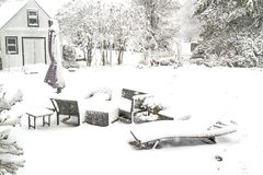 Lawnfurniture on patio covered in snow Stock Photo