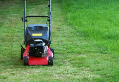 Lawnmower. Standing on green grass, partly mowed but part still left to mow Royalty Free Stock Photography