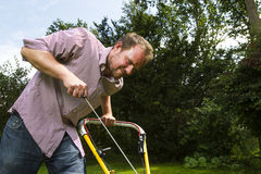 Lawnmower. Man trying to start a lawnmower Royalty Free Stock Photos