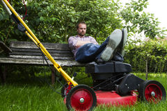 Lawnmower. Man sitting on bench resting legs on lawnmower Stock Photography