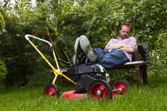 Lawnmower. Man sitting on bench resting legs on lawnmower Royalty Free Stock Images