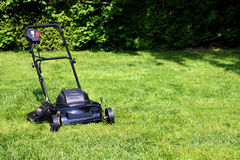 Lawnmower. Black lawnmower on freshly cut backyard grass Royalty Free Stock Images