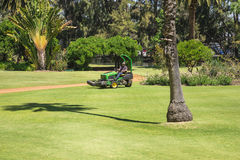 A lawnmower cutting grass in a Government House landscaped park Stock Photography