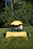 Lawnmower cutting long grass in a backyard. Close up of the mower Royalty Free Stock Image