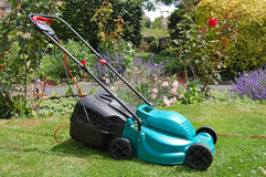 Lawnmower in garden Stock Images