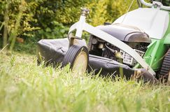 Lawnmower in the garden cutting lawn Royalty Free Stock Photos