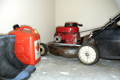 Lawnmower and gas can. Lawnmower stored in a garage with a gas can and boots stock photography