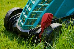 Lawnmower on the green grass working on a sunny day stock image