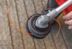 Lawnmower head trimmer for grass like garden machine holding. By a man Stock Images