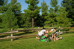 Lawnmower Inspection. The guys check out a new lawnmower in the backyard Stock Photo