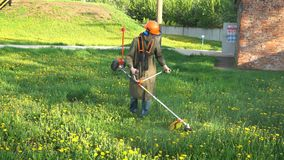 Lawnmower man mows the grass outdoors stock footage