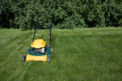 Lawnmower mowing grass with space for copy. On the right Stock Photos