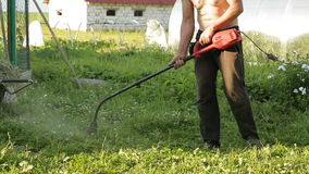 Lawnmower mowing grass. Worker mows green grass manual lawnmower. trimming lawns stock video footage