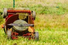 Lawnmower velho quebrado na grama do quintal Imagem de Stock Royalty Free