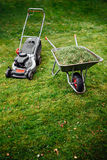 Lawnmower and wheelbarrow with grass on mown lawn Royalty Free Stock Images