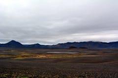 Lawowy pole w Iceland Dettifoss spadków terenie na tle odległe góry i burzowy niebo Zdjęcie Royalty Free