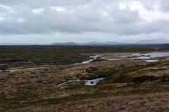 Lawowy pole w Iceland Godafoss spadków terenie na tle odległe góry i burzowy niebo Obraz Stock