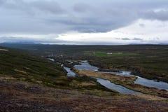 Lawowy pole w Iceland Godafoss spadków terenie na tle odległe góry i burzowy niebo Zdjęcia Royalty Free