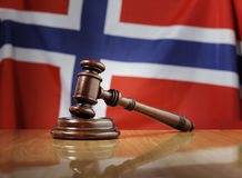 Laws of Norway. Mahogany wooden gavel on glossy wooden table, flag of Norway in the background Stock Photos