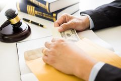 Lawyer being offered receiving money as bribe from client at desk in courtroom.  royalty free stock photo