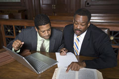 Lawyer With Businessman In Court. Lawyer discussing case with businessman while sitting in the courtroom royalty free stock image