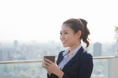 Lawyer businesswoman professional walking outdoors drinking coffee from disposable paper cup. Multiracial Asian / Caucasian royalty free stock photos
