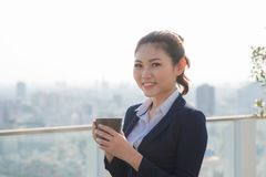 Lawyer businesswoman professional walking outdoors drinking coffee from disposable paper cup. Multiracial Asian / Caucasian. Businesswoman smiling stock images