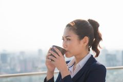 Lawyer businesswoman professional walking outdoors drinking coffee from disposable paper cup. Multiracial Asian / Caucasian stock image