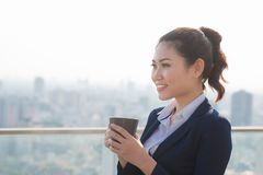 Lawyer businesswoman professional walking outdoors drinking coffee from disposable paper cup. Multiracial Asian / Caucasian stock photography