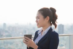 Lawyer businesswoman professional walking outdoors drinking coffee from disposable paper cup. Multiracial Asian / Caucasian royalty free stock photography