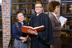 Lawyer and businesswoman standing near library. With law book Stock Photos