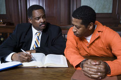 Lawyer With Criminal In Court. Male lawyer sitting with criminal in the courtroom Stock Photos