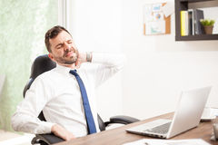 Lawyer dealing with neck pain in an office. Portrait of a young lawyer with a beard suffering from neck pain in the office due to a bad sitting posture royalty free stock image
