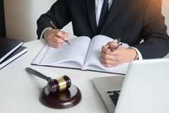 Lawyer hand writes the document in court & x28;justice, law& x29; with sou. Nding block Royalty Free Stock Photo