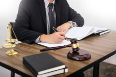Lawyer hand writes the document in court & x28;justice, law& x29; with sou. Nding block and golden Weight Royalty Free Stock Images