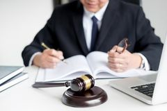 Lawyer hand writes the document in court & x28;justice, law& x29; with sou. Nding block Royalty Free Stock Images