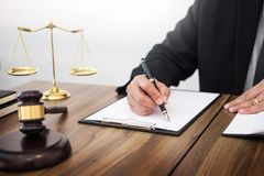 Lawyer hand writes the document in court & x28;justice, law& x29; with sou. Nding block and golden Weight Stock Photo
