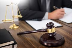 Lawyer hand writes the document in court (justice, law) with sou. Nding block and golden Weight Stock Photo
