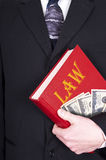 Lawyer Holding Law Book, Money, Corruption. Metaphor for the law, legal work, a lawsuit, and lawyers. A lawyer is holding a book of law but is also holding cash Stock Photography