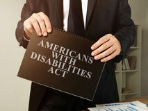 Free Lawyer Holds Americans With Disabilities Act ADA Book Royalty Free Stock Photos - 168703248