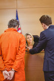 Lawyer and judge speaking next to the criminal in handcuffs Stock Photography