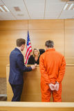 Lawyer and judge speaking next to the criminal in jumpsuit Royalty Free Stock Image
