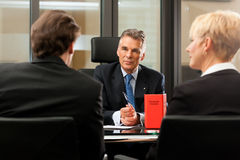 Lawyer or notary with clients in his office. Mature lawyer or notary with clients in his office in a meeting royalty free stock images