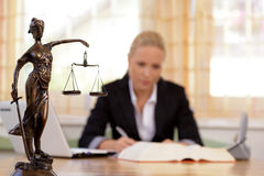Lawyer in the office. A young lawyer is sitting at her desk in the office royalty free stock photo