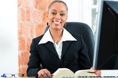 Lawyer in office with law book and computer. Young female black lawyer working in her office and reading a typical law book in front of a computer Royalty Free Stock Images