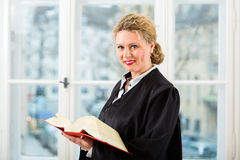 Lawyer in office with law book reading by window. Young female lawyer working in her office reading in a typical law book royalty free stock photography