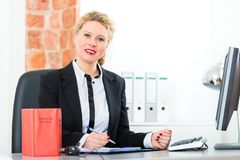 Lawyer in office with law book working on desk. Young female lawyer working in her office with typical law book and writing document royalty free stock photo